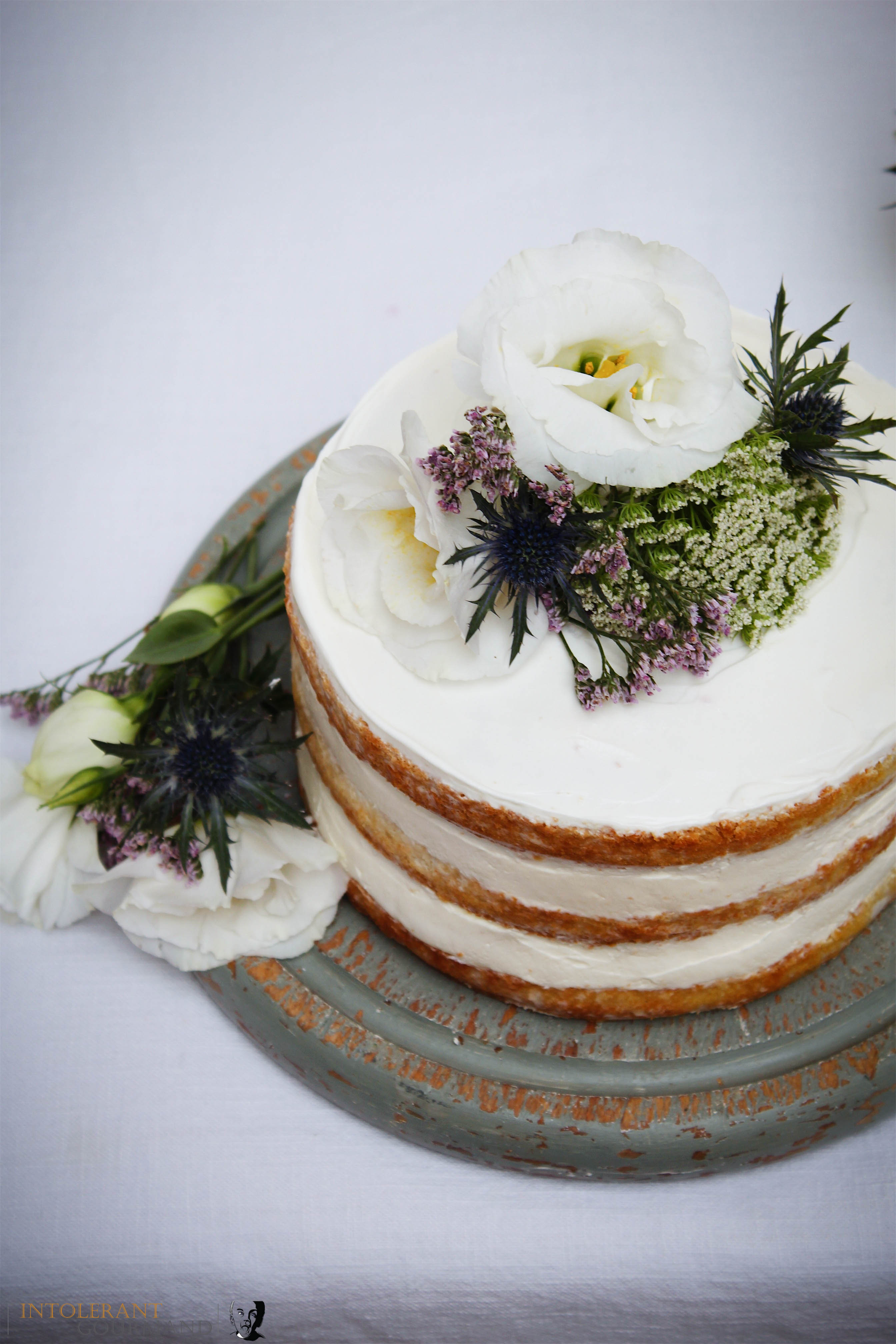 Royal Wedding Cake - Elderflower and Lemon. A beautiful 3 tiered naked cake, covered with smooth buttercream and finished off with fresh flower decorations. Flavoured with elderflower and lemon and perfect for any celebration! It is also gluten-free! www.intolerantgourmand.com