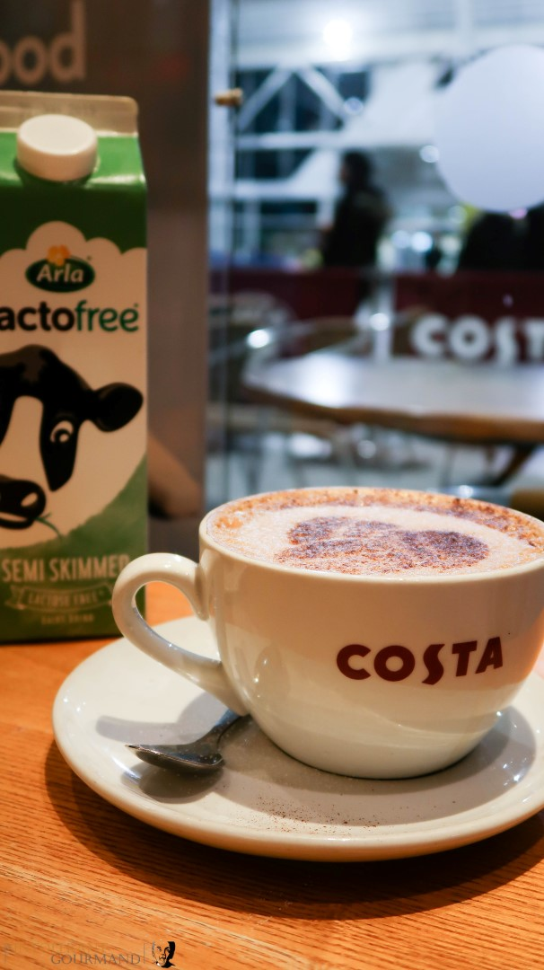 A large white cup of latte coffee made with Arla Lactofree milk on a table, with a carton of Arla Lactofree milk in the background, and available at Costa coffee now! www.intolerantgourmand.com