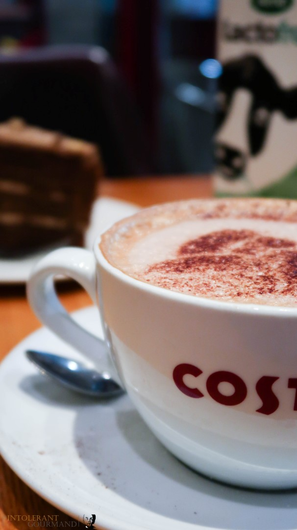 A large cup of latte coffee with a slice of coffee and walnut cake in the background. All available at Costa. www.intolerantgourmand.com