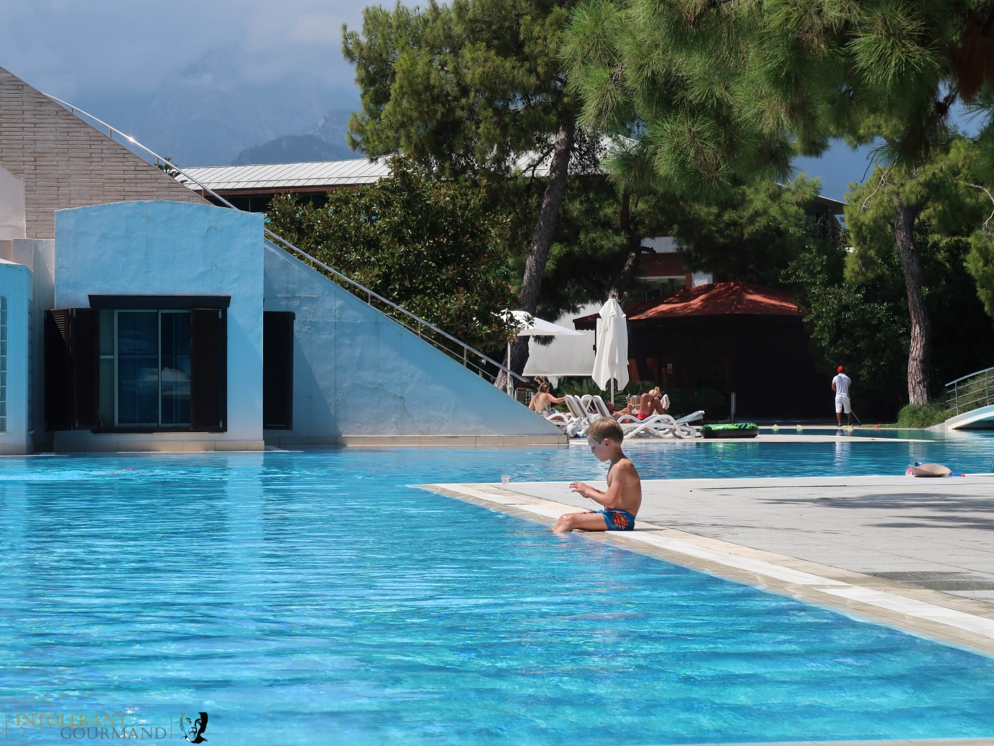 Rixos Sungate Kemer Antalya with Jet 2 Holidays - little boy sat on the side of a quiet swimming pool, contemplating. www.intolerantgourmand.com