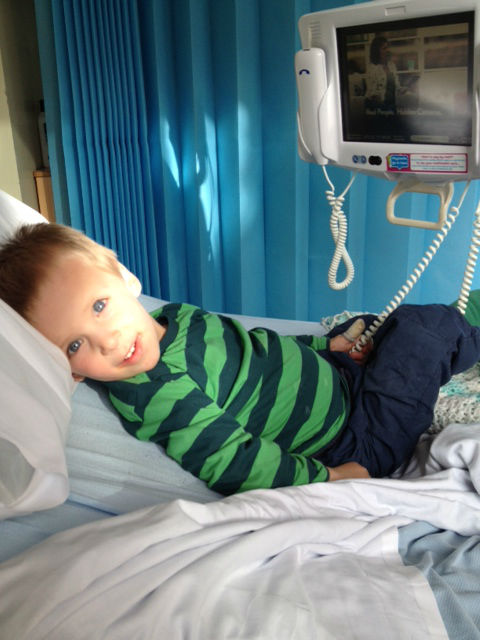 Callum in hospital, requiring a nebuliser to regulate his breathing, sat on a hosital bed, looking at me, with the sun shining on him. www.intolerantgourmand.com