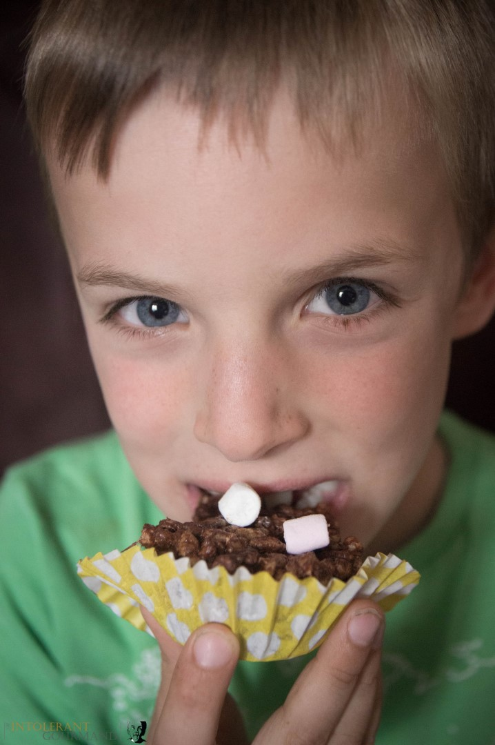 Callums chocolate crispie cakes as seen on the BBC - Callum biting into a chocolate crispie cake! www.intolerantgourmand.com